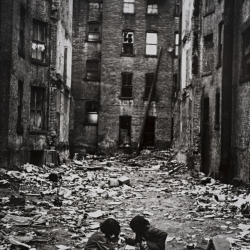 Kids playing amid debris between buildings