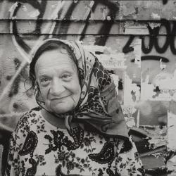 Elderly woman in headscarf against graffiti, Rome, Italy