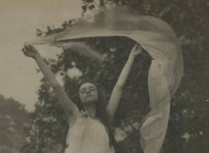 Untitled [Woman in ballet shoes, tights, and dress holds up gauze above head with both hands]