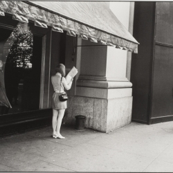 Woman Reading Newspaper by Store Window